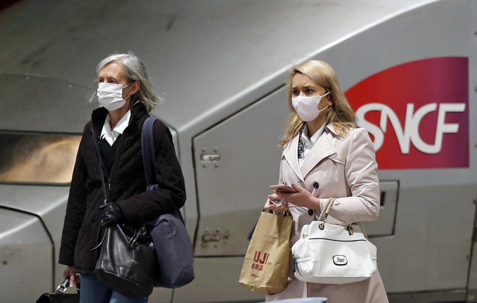 Passengers wearing protective face masks walk past a TGV (high speed train) at the Gare Montparnasse in Paris