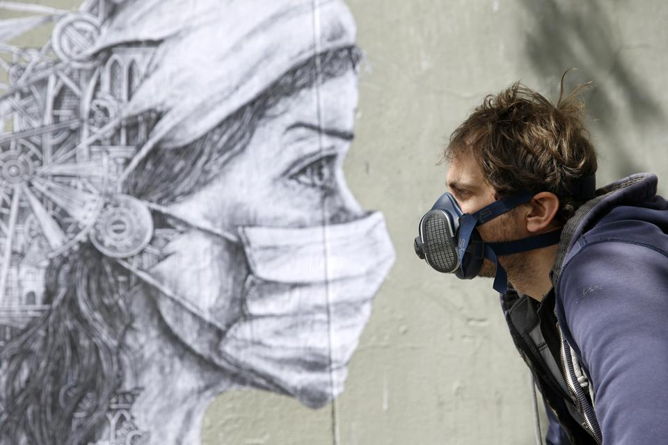 French street artist Ardif in front of his artwork to pay tribute to medical workers on May 12, 2020 in Paris, France.