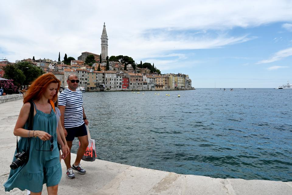 Tourists wander by Adriatic sea in Croatia as EU borders open for travel also Americans