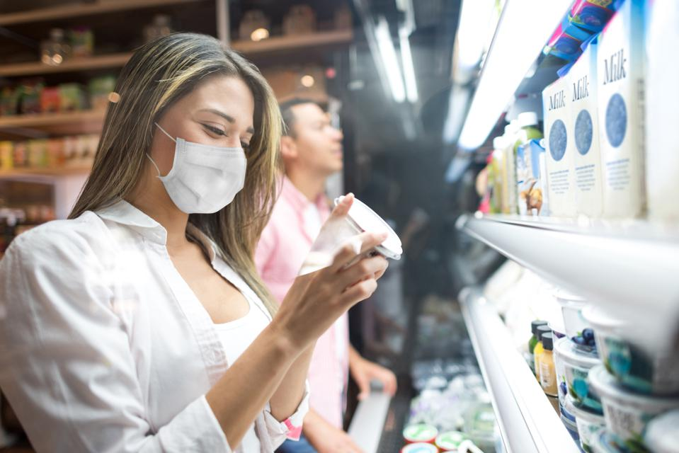 Woman grocery shopping at the supermarket wearing a facemask