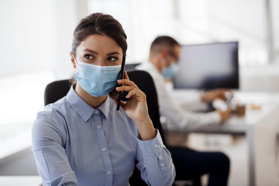 Young businesswoman with face mask talking on the phone while working in the office. stock photo