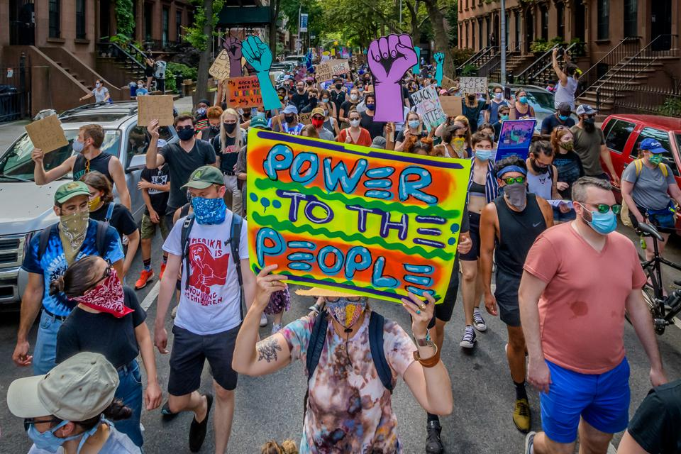 A participant holding a Power To The People sign at the...