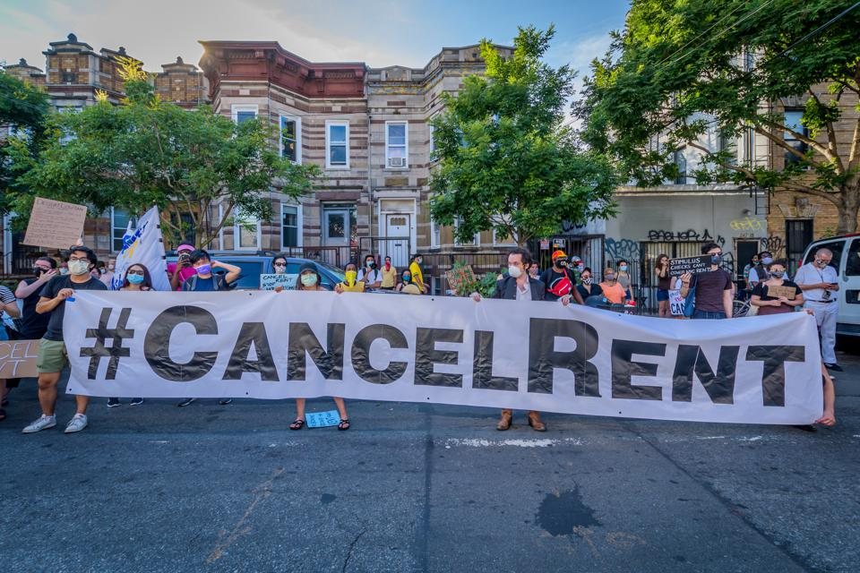 Participants hold a #CancelRent banner at the protest.