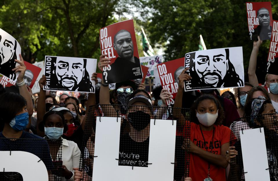 Demonstrators hold up banners bearing the likenesses of Philando Castile and George Floyd during a protest march on July 6, 2020 in St. Anthony, Minnesota.