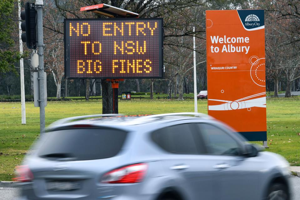 car drives past No Entry BIG FINES sign in new south wales australia as it closes border
