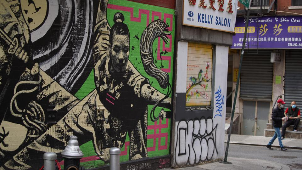 people on street of chinatown in new york city near street art