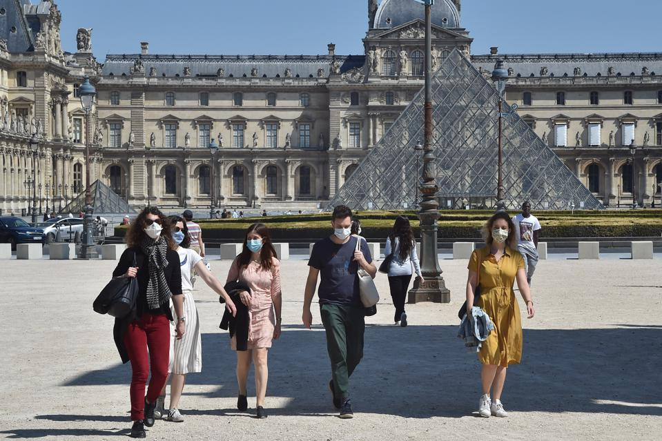People wearing protective face masks walk next to the closed Louvre Museum after France eased lockdown measures taken to curb the spread of the COVID-19 pandemic on May 17, 2020 in Paris France.