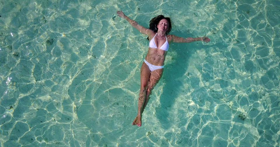 Top view of a beautiful woman staying afloat in the water under the warm sun