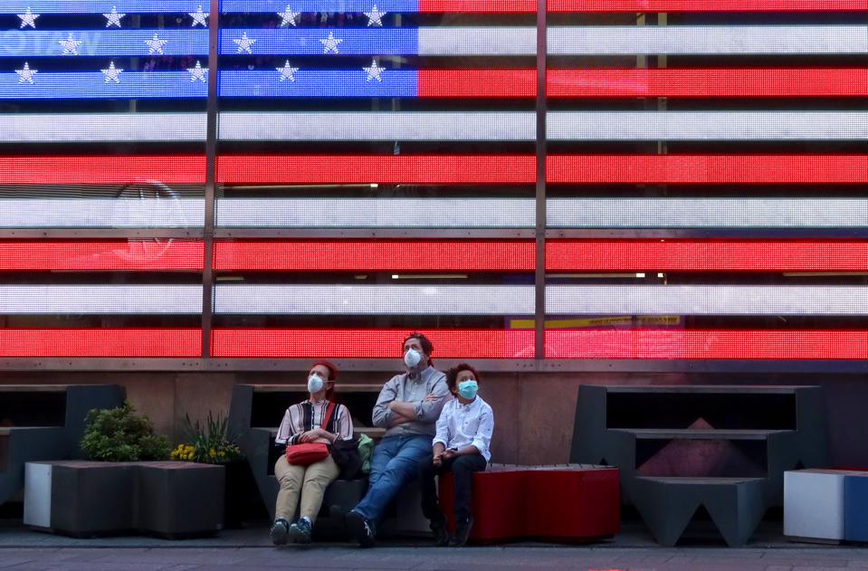 Americans wear masks as they sit under American flag in Times Square New York US