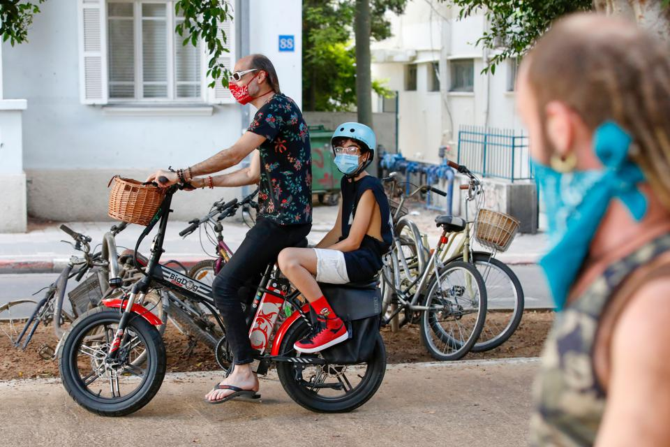 A man and a youth wearing protective Covid-19 masks ride bike  in Tel Aviv Israel
