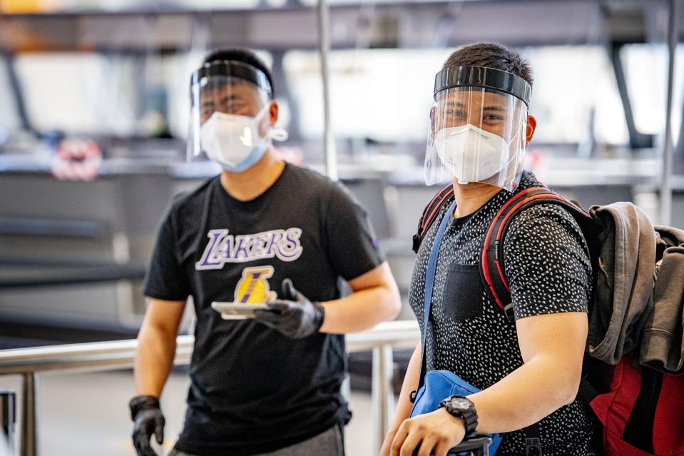 Men wearing face shields at the airport in Europe but no US Americans with EU travel ban