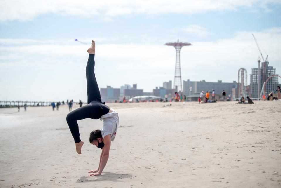 A woman wearing a mask poses doing yoga on the beach at Coney Island