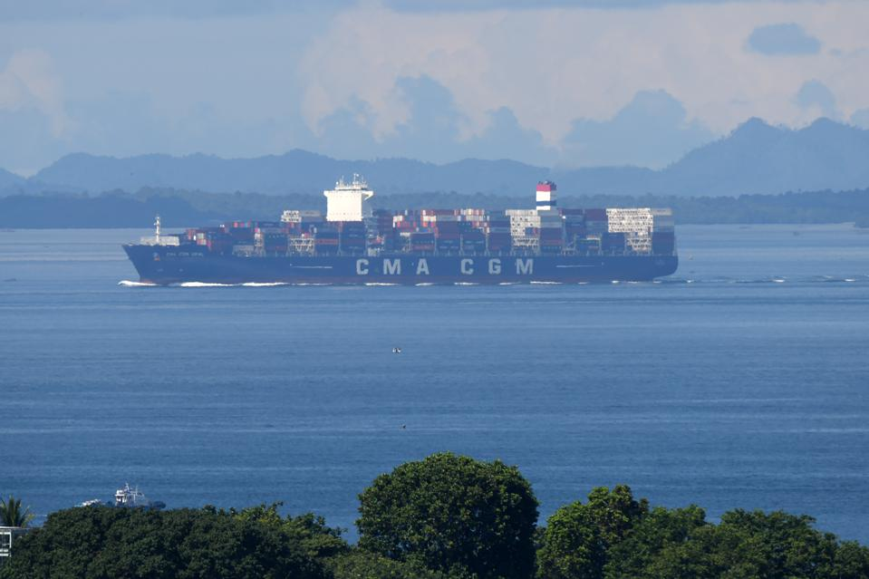 A container vessel leaves the port of Singapore.