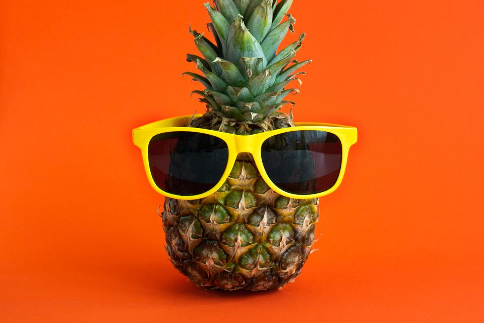 Pineapple on a bright orange background with yellow glasses