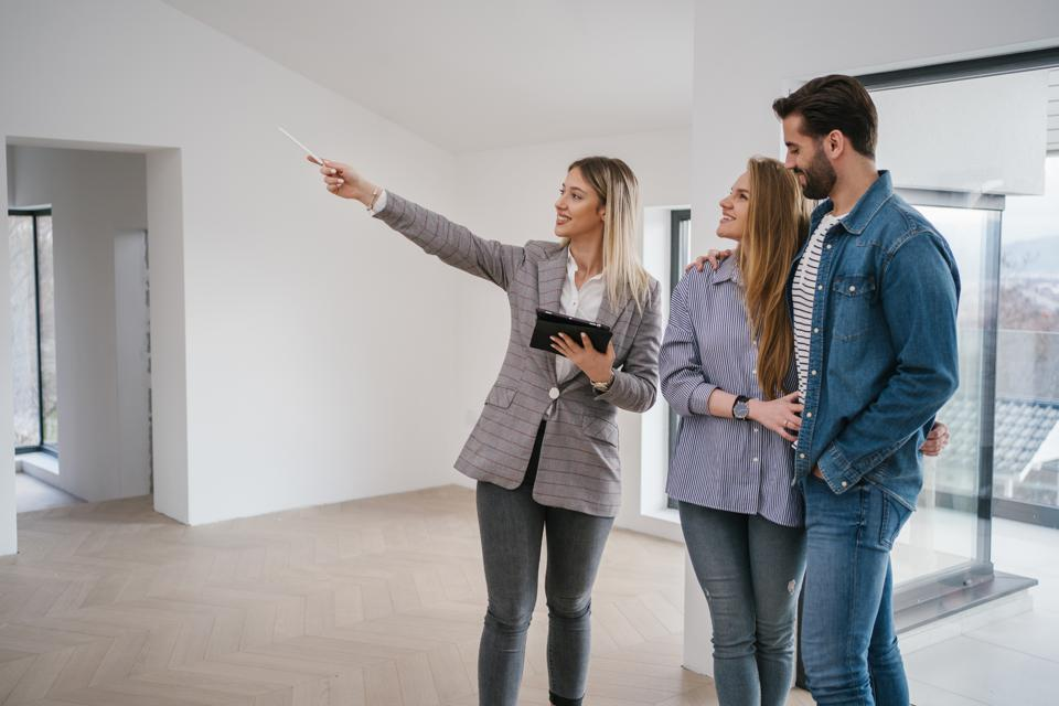 Joyful female estate owner selling a house to a young couple