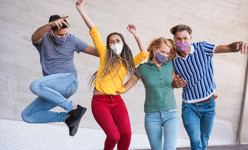 Young people having fun around city street during coronavirus outbreak - Happy friends wearing face protective masks and laughing together - Main focus on girls faces