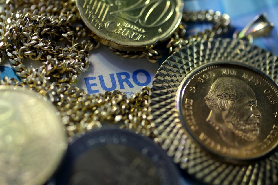 A gold necklace and a coin with an Euro note and coins