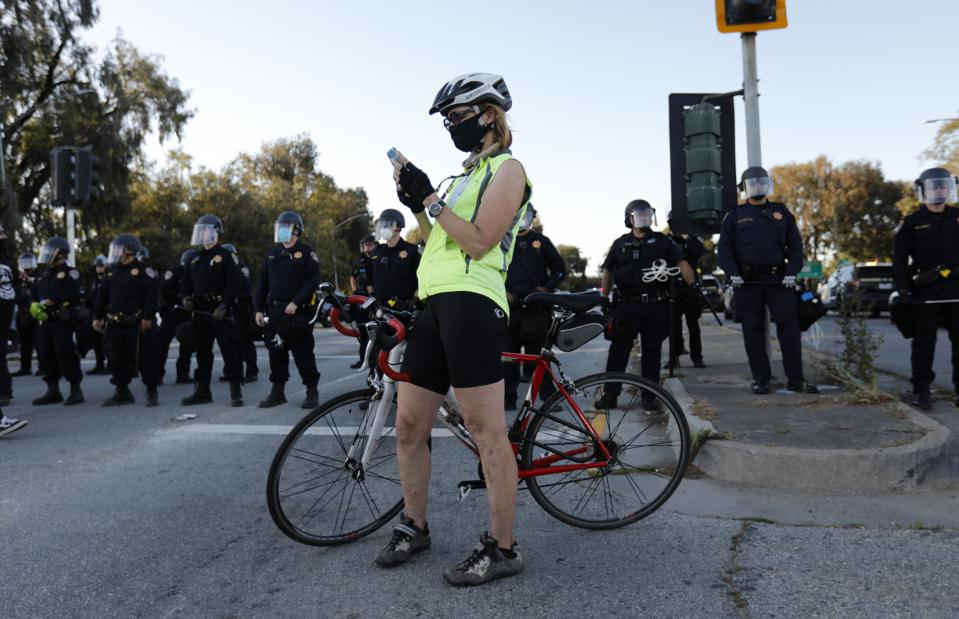 A bicyclist checks her cellphone in front of officers during a protest