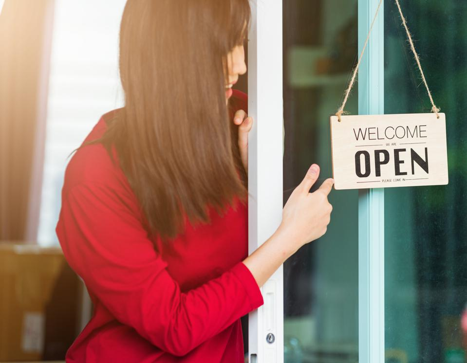 New normal, Asian young woman glad and smiling point finger to notice sign wood board label ″WELCOME OPEN″ hang through glass door front shop, Business turning open after coronavirus pandemic disease