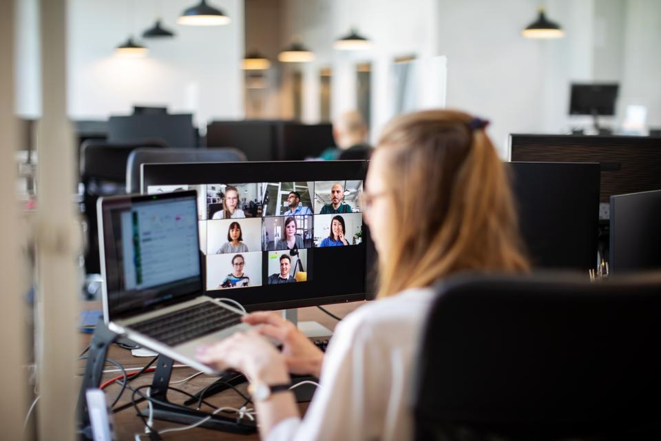 Woman discussing work on video call with team members at office