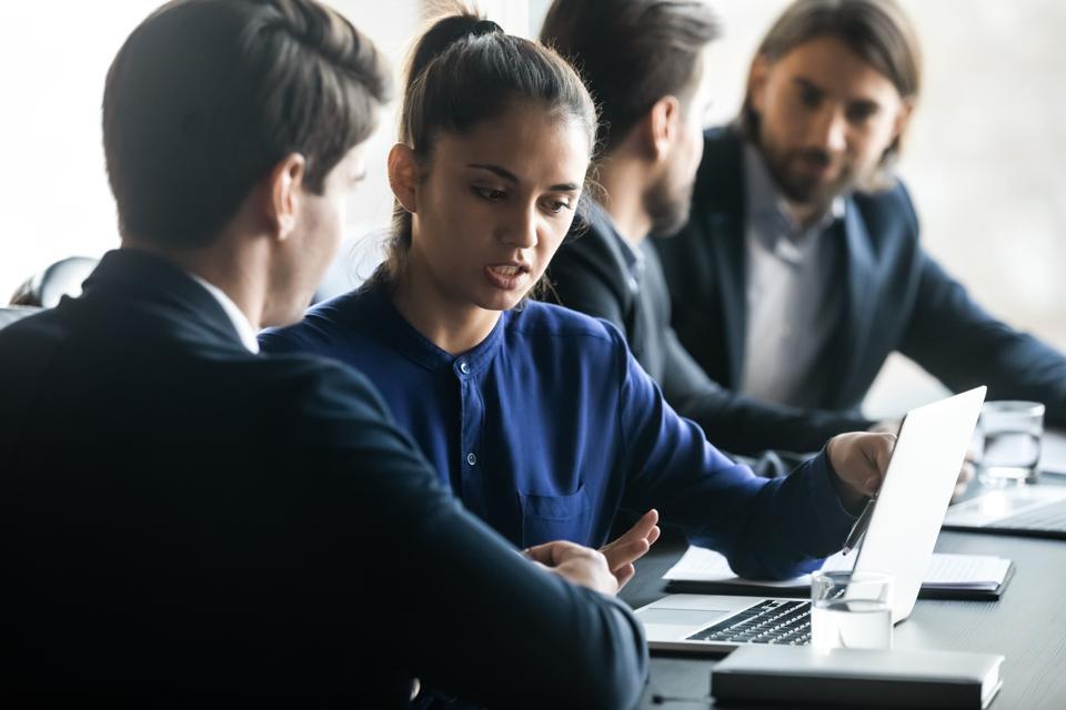 Confident businesswoman mentor training intern, using laptop in boardroom