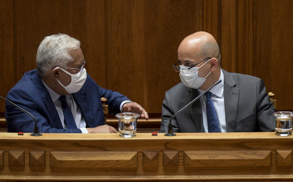 Two masked legislators debate drug prices during the coronavirus pandemic.