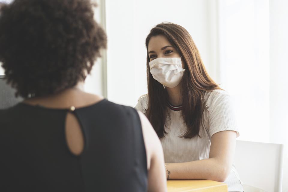 Two young women talking in an office wearing a protective face mask.