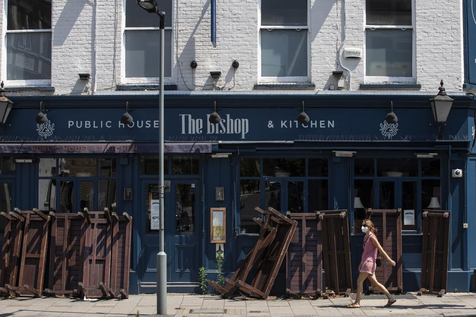 A woman wearing a face mask walks past a closed pub in Dulwich on June 24, 2020 in London, England.
