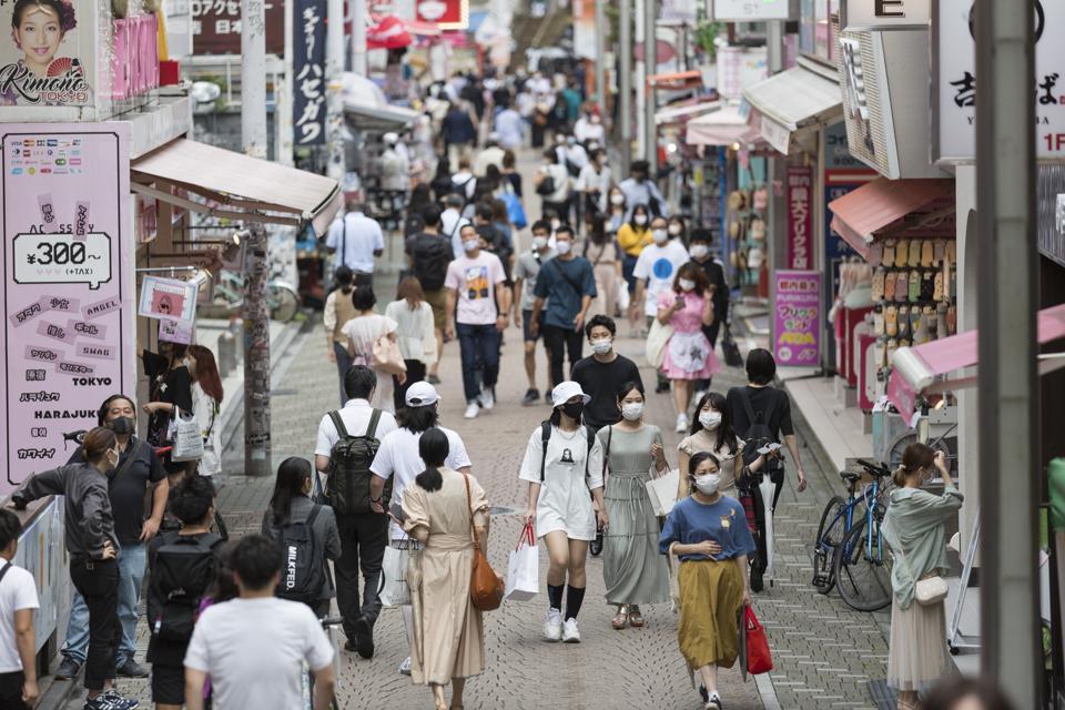 People wearing face masks walk down Takeshita street in Tokyo, Japan.