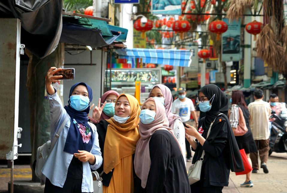 Girls in masks in Petaling Street Chinatown  as it Reopens In Kuala Lumpur malaysia