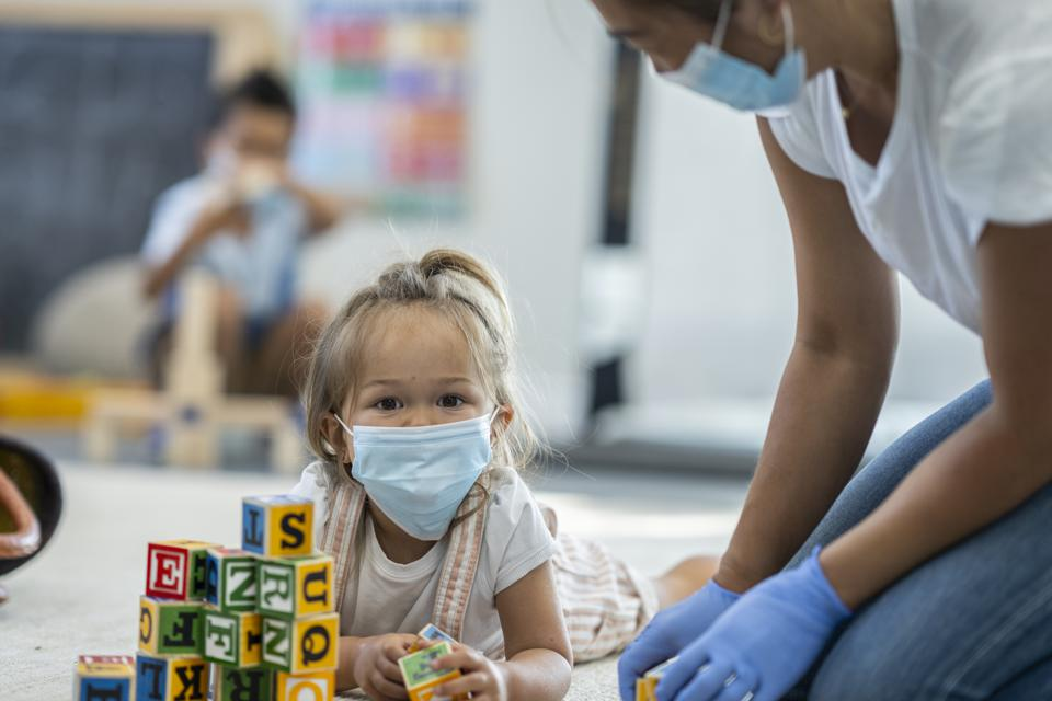 Young girl playing at daycare wearing a protective mask