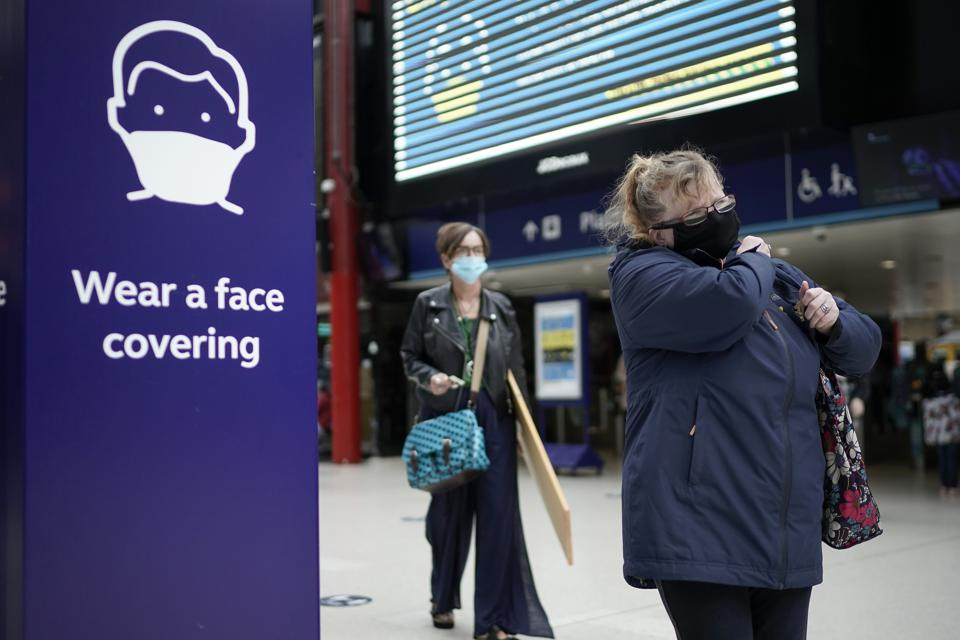 People wear face masks at Liverpool train station in England, UK, rules mandatory