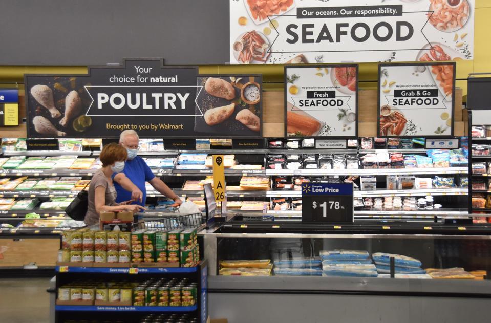 Customers wearing face masks shop at a Walmart supermarket amid novel coronavirus outbreak on July 15, 2020 in Washington, DC