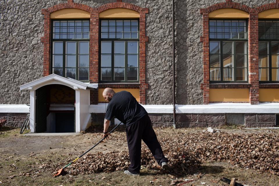 An inmate raking leaves at Norway's Bastøy prison.