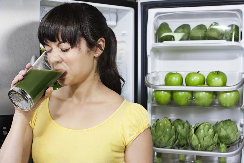 Grimacing woman drinking healthy drink near refrigerator