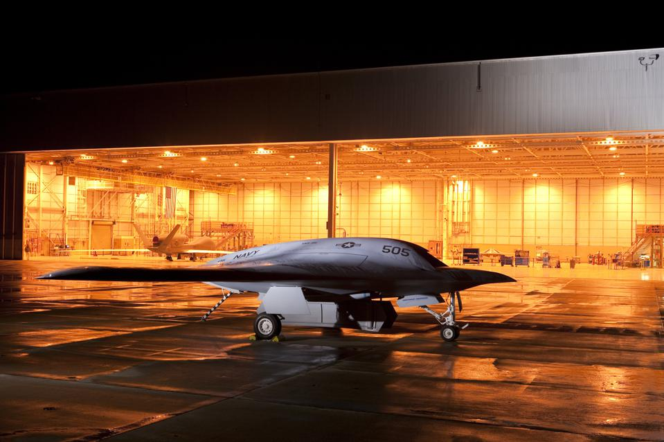 Northrup Grumman's mock-up of the company's newest unmanned combat air vehicle, the X-47B, shown with its bomb doors open and aircraft carrier tailhook deployed. At left in hangar, the fully autonomous Global Hawk reconnaissance vehicle.