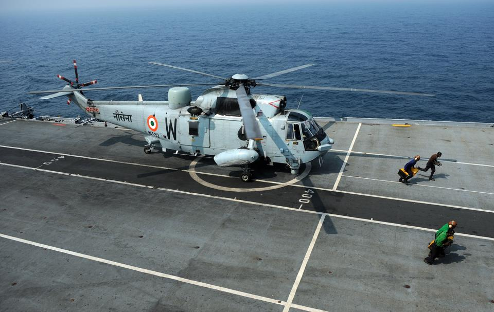 Indian sailors move away from a Sea King