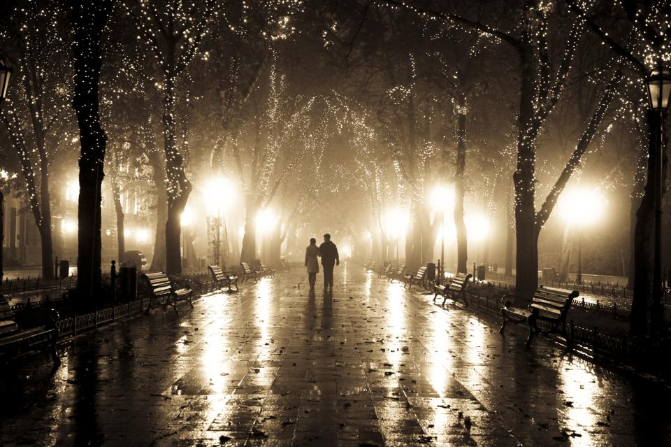 Couple walking at alley in night lights.