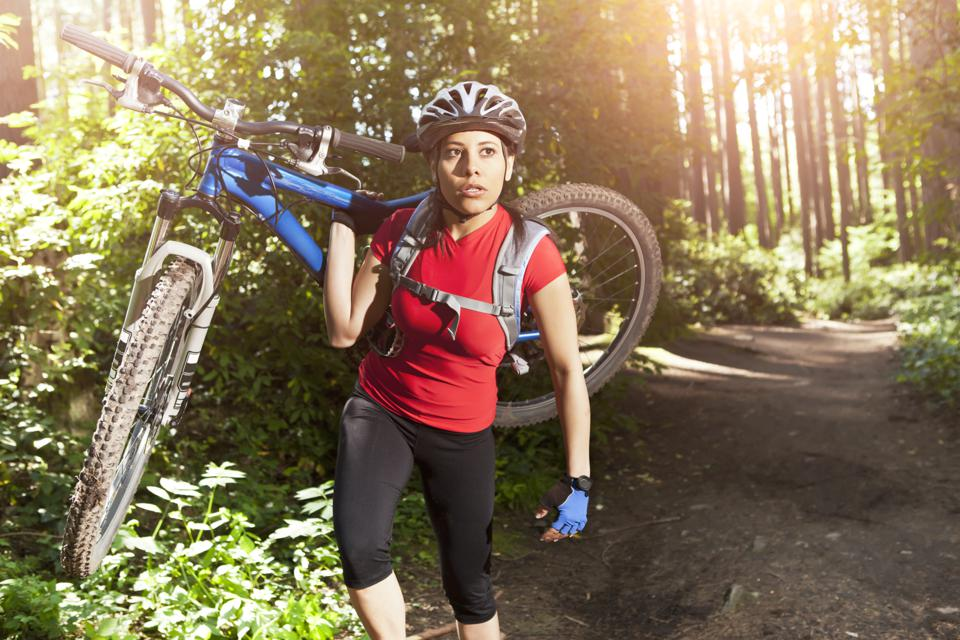 Woman carrying mountain bike in forest