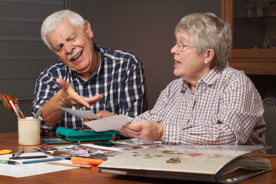 Senior couple choosing photos for scrapbook album