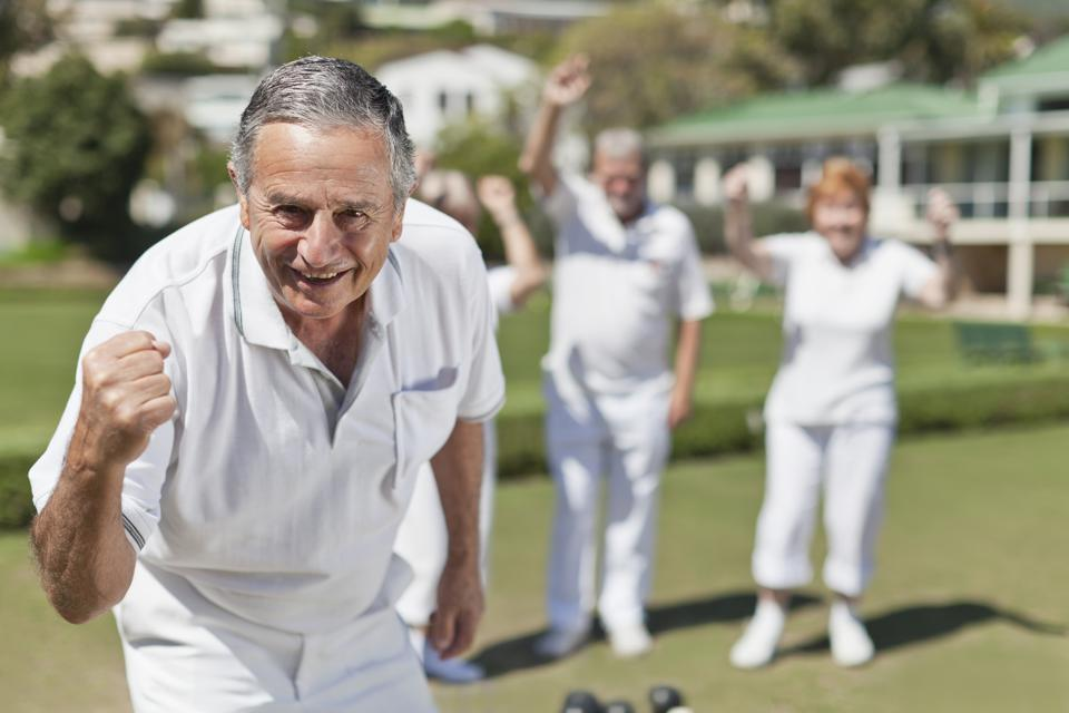 Older people playing lawn bowling
