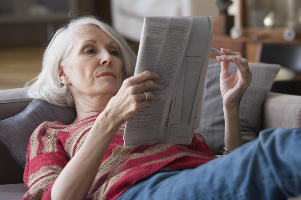 Elderly woman doing newspaper crossword puzzle