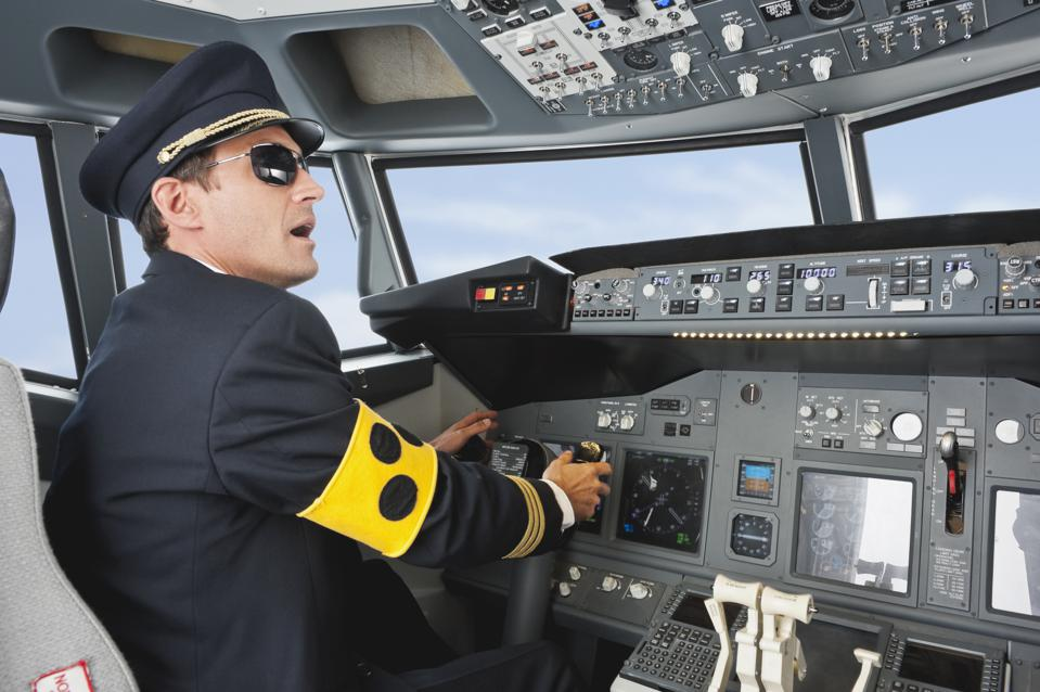 Germany, Bavaria, Munich, Pilot with armlet for blind piloting aeroplane from airplane cockpit