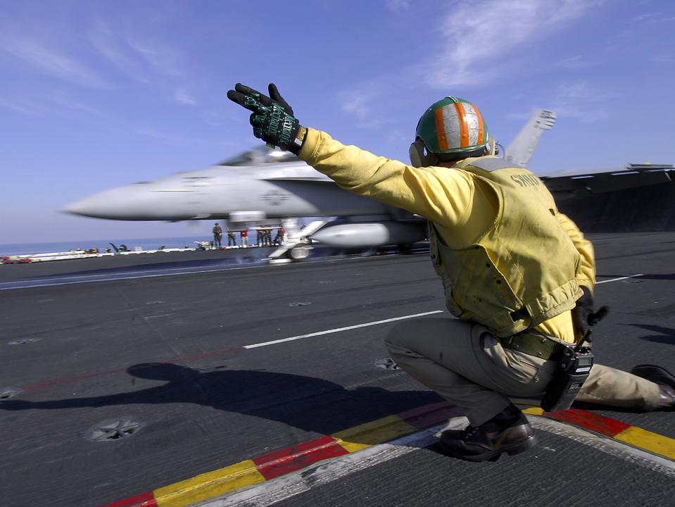 A shooter signals the launch of an F/A-18 Super Hornet.