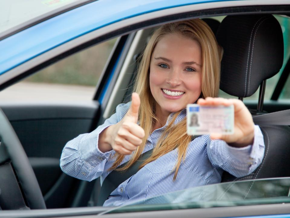 Attractive woman in car showing her drivers license