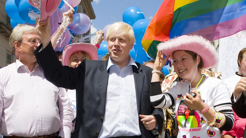 Boris Johnson Plans To Make Changing Gender Harder In Blow For Trans Rights – Boris at London Pride holding pink hat, with blue balloons in colours of trans flag and lgbt flag flying