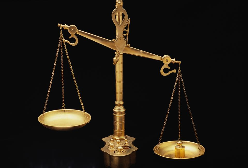 These are the golden Scales of Justice. They represent the legal system and courts. The scales here are shown unbalanced with the left side weighing heavier than the right. They are shown against a black background.