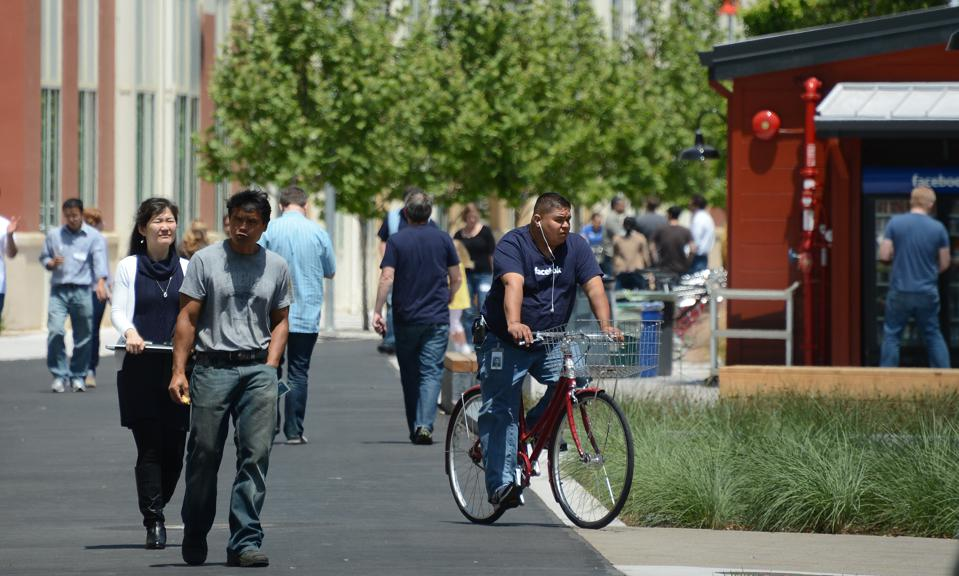 People walk and ride bicycles at the Fac