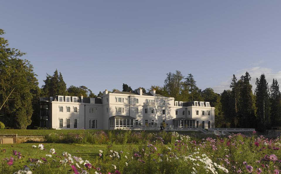 white country mansion surrounded by gardens and trees