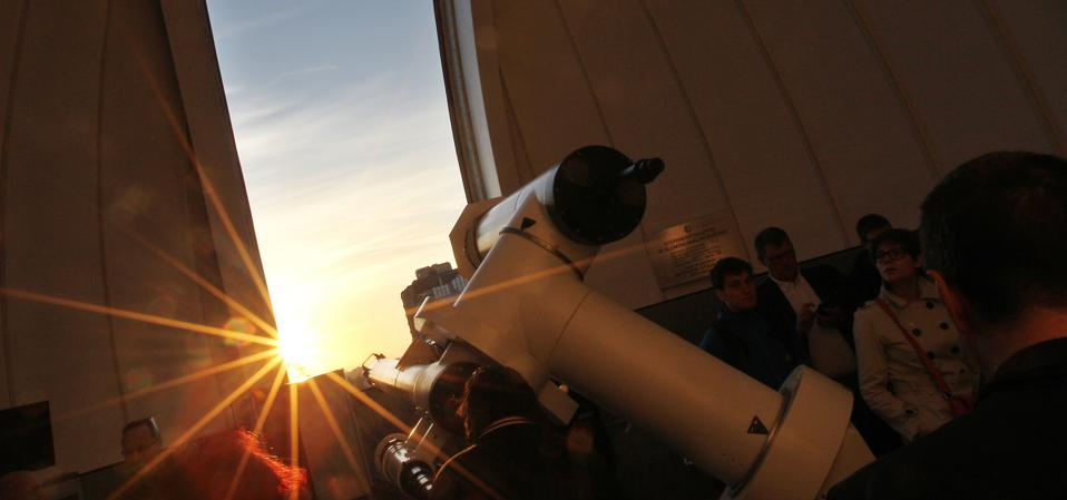 People use a telescope to see Venus transit across the Sun at the Vienna Urania observatory in Vienna on June 6, 2012. AFP PHOTO / ALEXANDER KLEIN